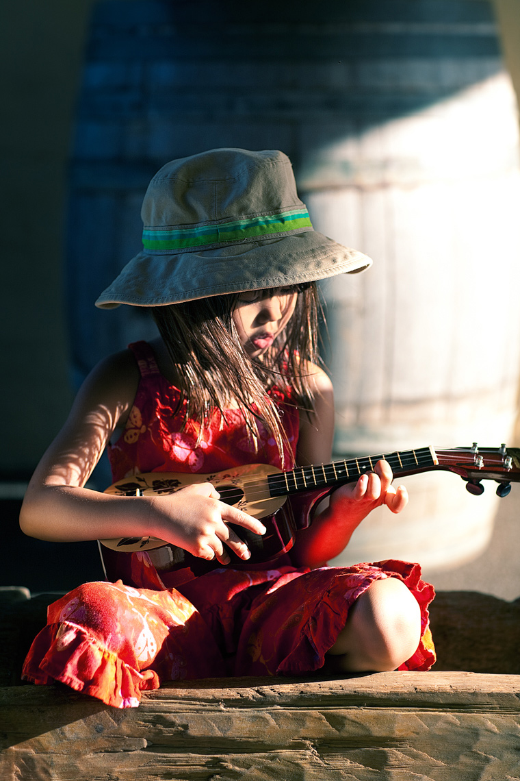 Young girl playing ukulele Portrait by commercial celebrity photographer Michael Grecco